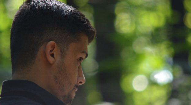 Maahanmuuttajataustainen mies kävelee metsässä
