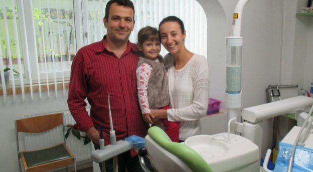 Kristitty hammaslääkäri Ema Stancius klinikallaan, jonka kaikki laitteet on lahjoitettu Suomesta. Kuvassa myös Eman aviomies Silvio ja tytär Pianca.