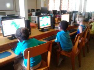 Lapset opiskelevat tietokoneluokassa.