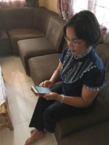 Rouva Juita lukee Raamatun tekstiä kännykästä.