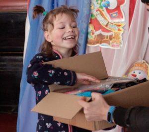 Lapsi on saanut lahjalaatikon. Kuva: Idän kirjallisuustyön arkisto