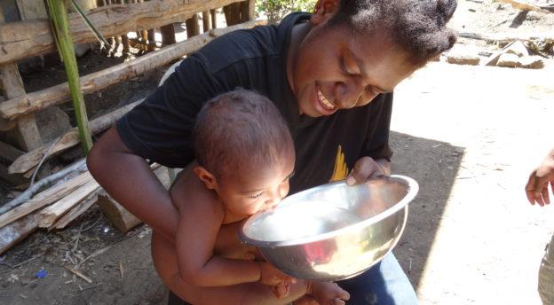 Lapsi juo vettä äitinsä sylissä.