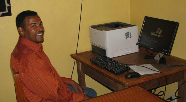 Alemayehu istuu työpöytänsä ääressä vuonna 2008, jolloin hän sai ensimmäisen tietokoneensa toimiessaan raamattukoulun rehtorina. Kuva: Aki Tuppuraisen arkisto