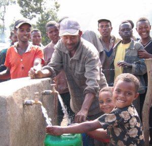 Lapset ottavat puhdasta vettä suojatusta lähteestä. Kuva: Pirkko ja Aki Tuppuraisen arkisto